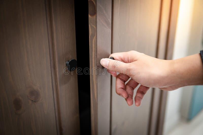Mão masculina que abre o armário de madeira fotografia de stock