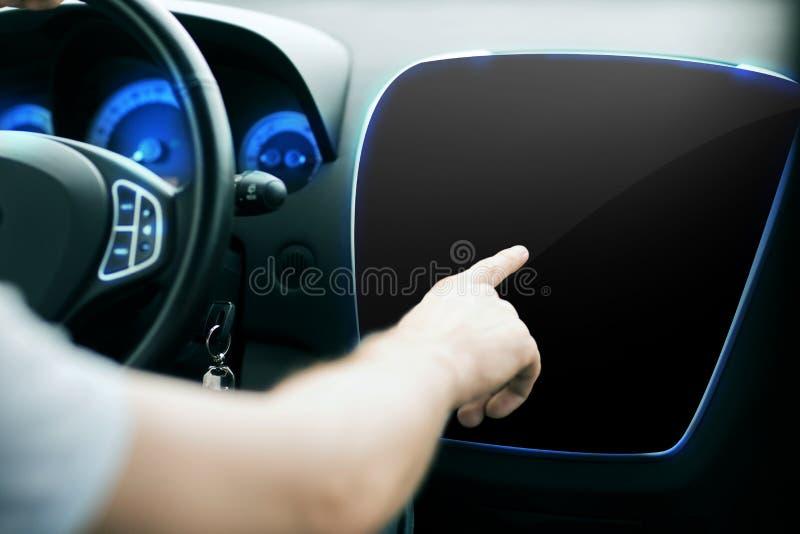 Mão masculina que aponta o dedo ao monitor no painel do carro fotos de stock