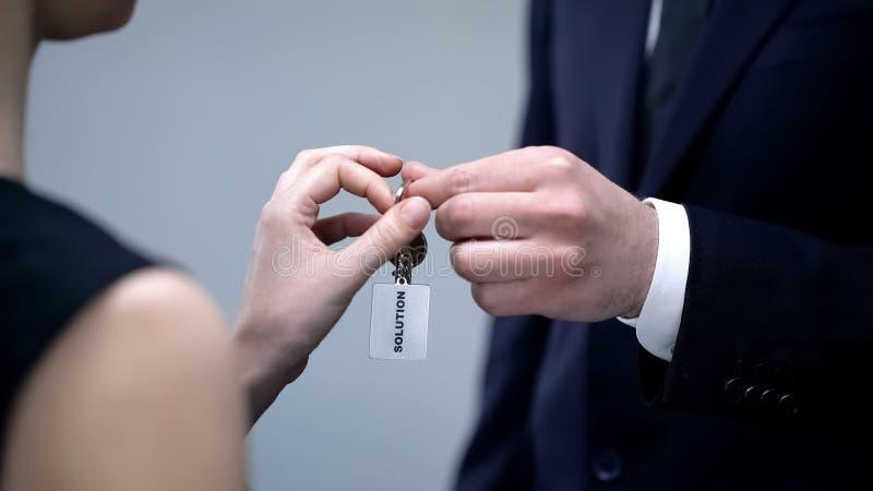 Mão masculina que dá chaves da senhora à solução, ajuda em resolver o close up do problema de negócio foto de stock royalty free