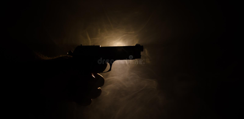A mão masculina que guarda a arma no fundo preto com fumo (branco amarelo do vermelho alaranjado) coloriu luzes traseiras, concei foto de stock