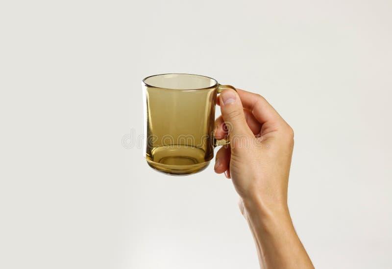 Mão masculina que guarda a caneca de vidro vazia preta no backgr cinzento fotos de stock royalty free