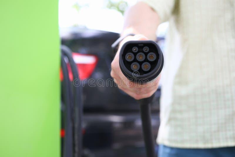 Mão masculina que guarda o cabo de carregamento do carro do carro preto foto de stock royalty free