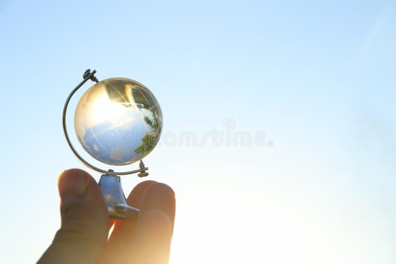 mão masculina que guarda o globo de cristal pequeno na frente do céu azul fotografia de stock royalty free