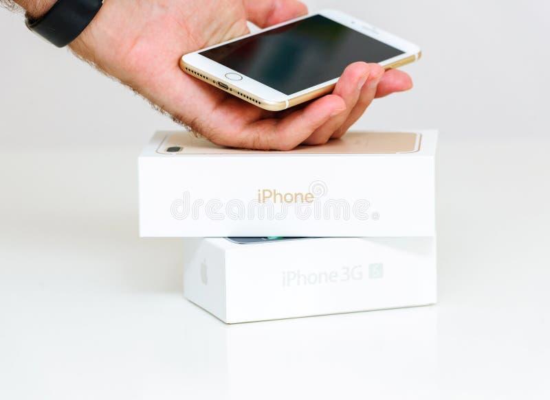 Mão masculina que guarda o iPhone novo de Apple 7 sinais de adição após unboxing com iPhone foto de stock