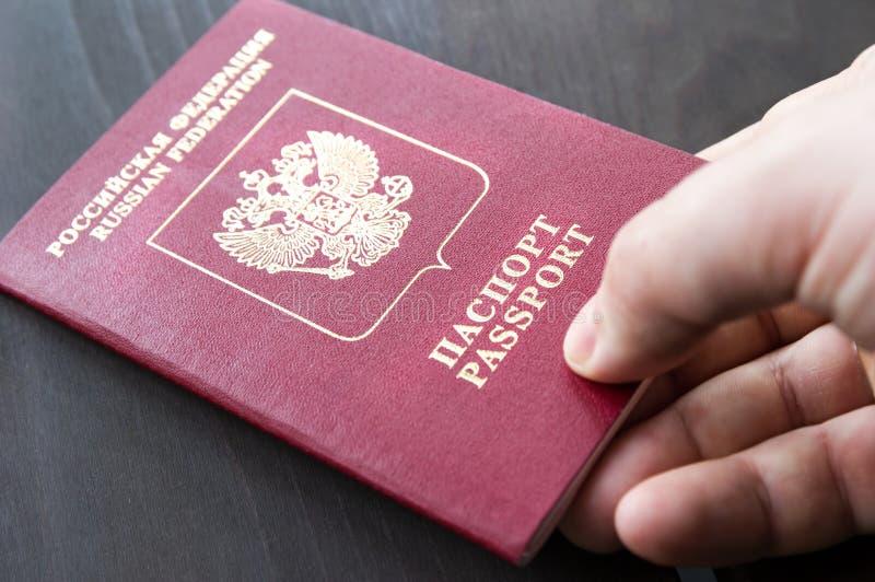 Mão masculina que guarda o passaporte vermelho Fundo de madeira cinzento fotos de stock royalty free