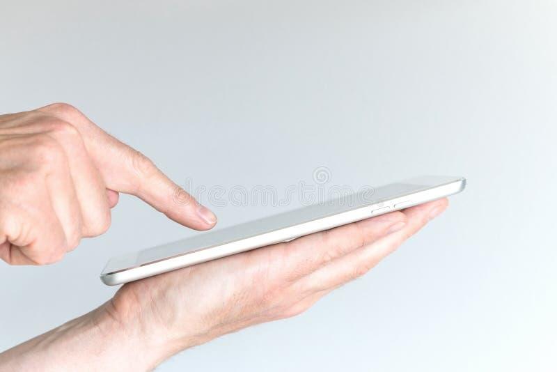 Mão masculina que guarda a tabuleta moderna ou o grande telefone esperto fotografia de stock