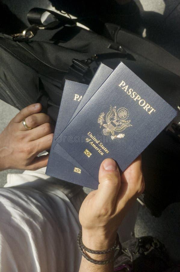 Mão masculina que guarda três U S passports fotografia de stock royalty free