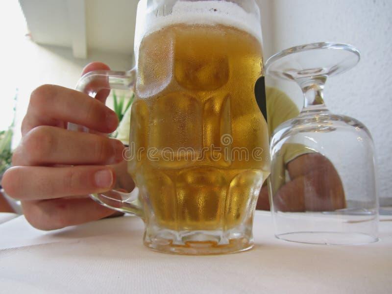 Mão masculina que guarda uma caneca fria de cerveja clara fotografia de stock royalty free