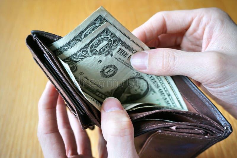 Mão masculina que guarda uma carteira de couro e que retira a moeda americana (dólares americanos de USD,) imagens de stock