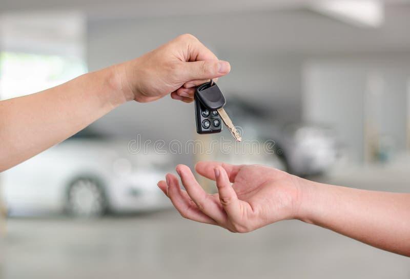 Mão masculina que guarda uma chave e entregar do carro imagem de stock
