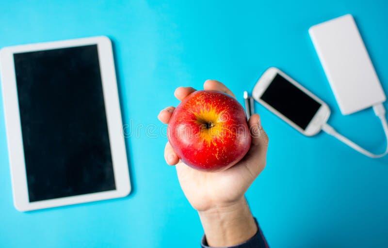 Mão masculina que guarda uma maçã com tabuleta e telefone celular foto de stock royalty free