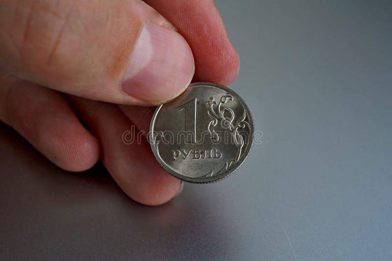 Mão masculina que guarda uma moeda de prata brilhante de uns rublo & x28; Rouble& x29; como o símbolo da moeda do russo imagem de stock