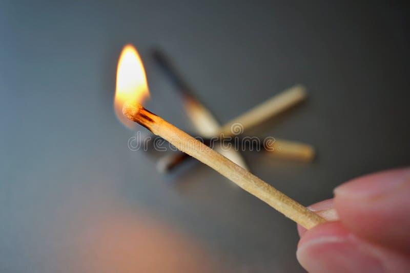 Mão masculina que guarda vara ardente do fósforo de segurança com uma chama que aproxima-se a mão foto de stock