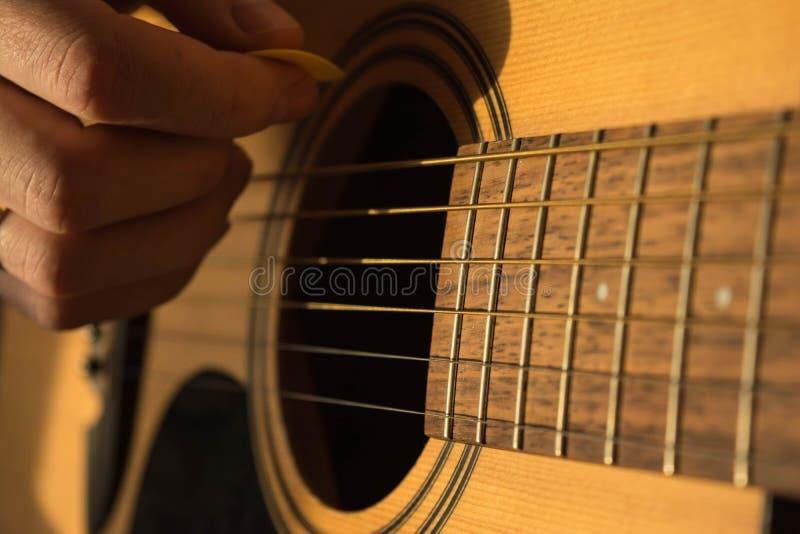 Mão masculina que joga a guitarra acústica na luz natural imagens de stock