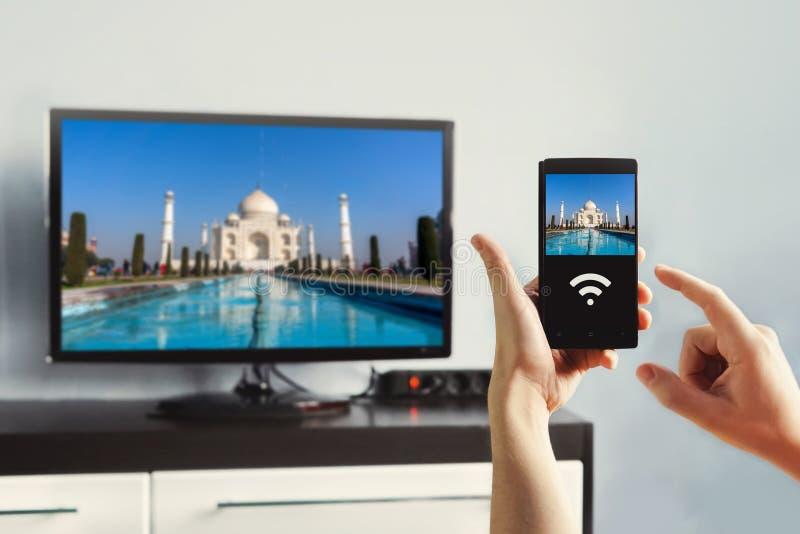 mão masculina que mantém um smartphone contra a vista da sala de visitas foto de stock