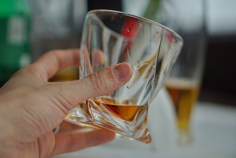 Mão masculina que mantém um uísque de vidro com licor dourado como um símbolo do álcool bebendo foto de stock