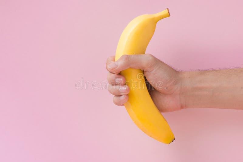 Mão masculina que mantém uma banana isolada no fundo cor-de-rosa imagem de stock