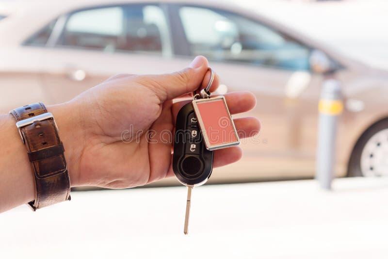 Mão masculina que mantém uma chave do carro contra o carro marrom fotos de stock royalty free