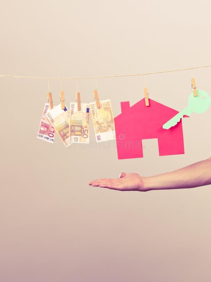 Mão masculina que mostra a casa e o dinheiro imagem de stock royalty free