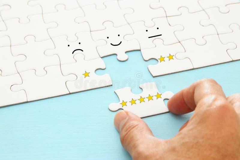 mão masculina que põe a última parte no enigma Imagem do conceito de ajustar um objetivo de cinco estrelas avaliação do aumento o imagens de stock