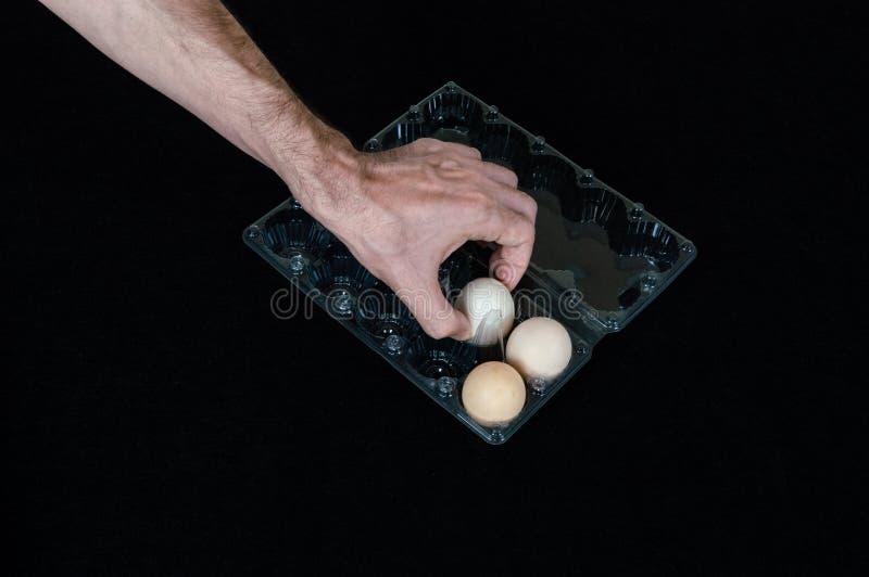 Mão masculina que toma um ovo da caixa de ovo plástica no fundo preto da esteira imagens de stock
