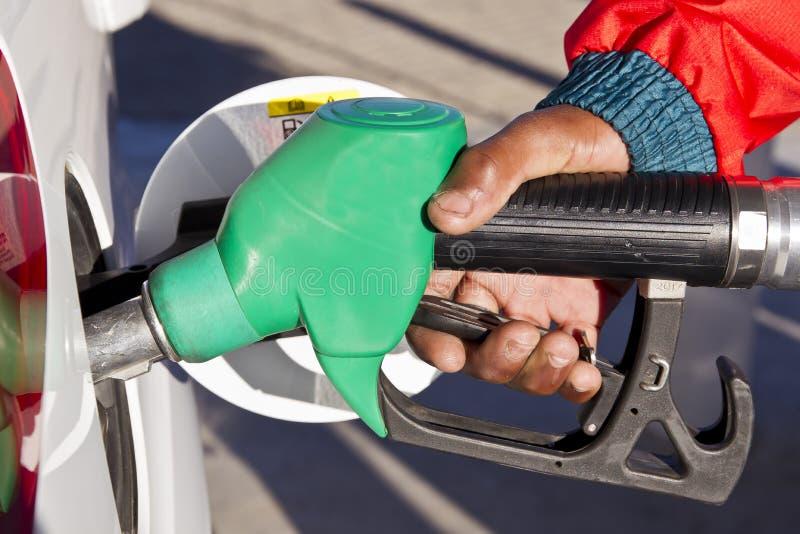 Mão masculina usando uma bomba de gasolina verde fotografia de stock royalty free