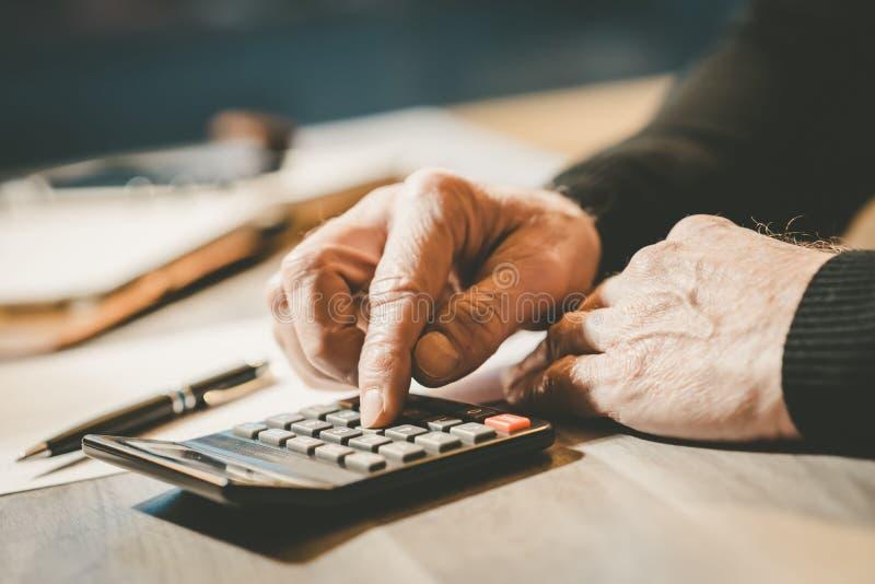 Mão masculina usando uma calculadora imagens de stock