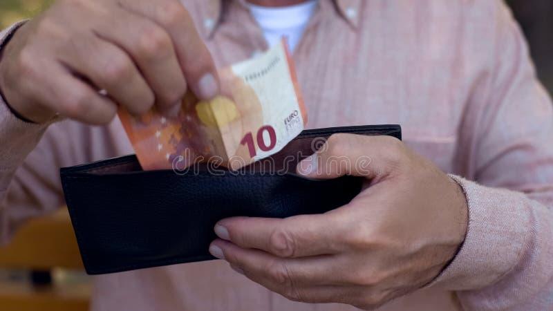 Mão masculina velha que põe a euro- carteira da conta, sistema do banco, pobreza do pensionista, orçamento fotografia de stock