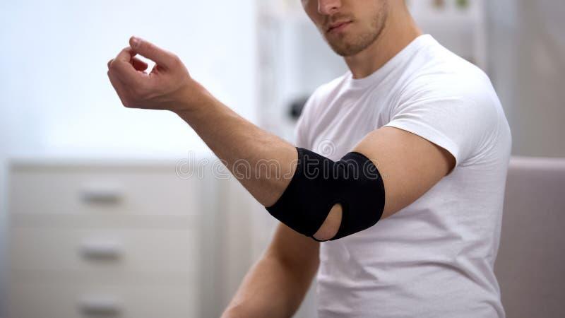 Mão movente do homem na ortose acolchoada cotovelo, recuperação após cuidados médicos do traumatismo do esporte fotografia de stock
