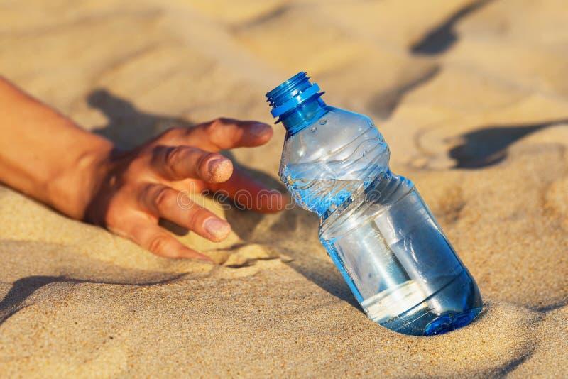A mão na areia alcança para uma garrafa da água potável Conceito da sede imagens de stock royalty free