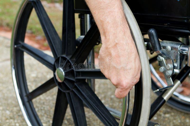 Mão na cadeira de rodas imagens de stock