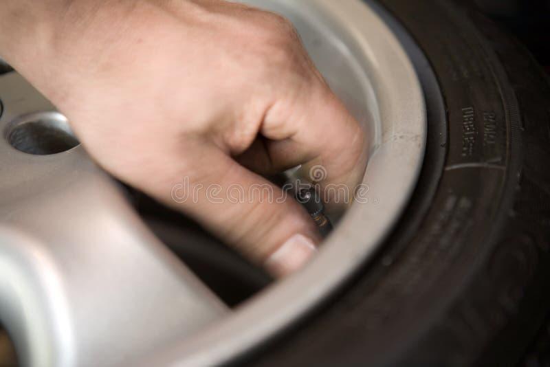 Mão na haste de válvula do pneu fotografia de stock