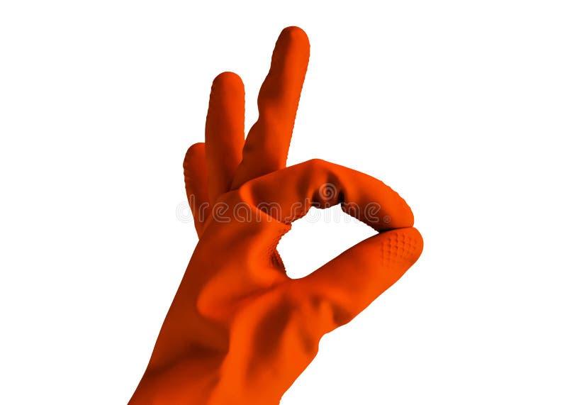 A mão na luva alaranjada de borracha mostra o sinal da aprovação, objeto isolado no fundo branco Conceito da limpeza fotografia de stock