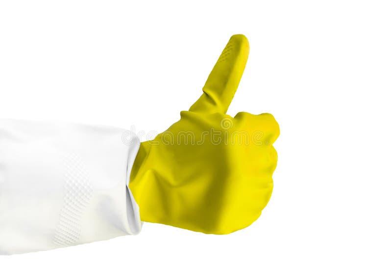 A mão na luva amarela de borracha mostra o sinal da aprovação, objeto isolado no fundo azul para o projeto com espaço da cópia imagem de stock royalty free