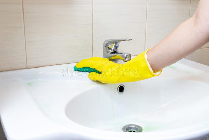 A mão na luva de borracha amarela lava o dissipador do banheiro com uma esponja Limpe o conceito fotos de stock royalty free