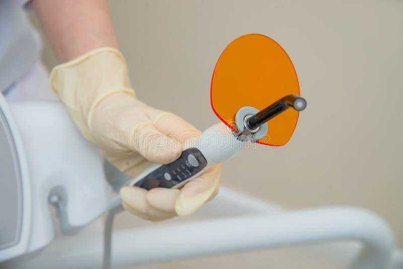 Mão na luva médica que guarda a luz de cura UV dental Lâmpada ultravioleta da polimerização com vidro de obstrução alaranjado foto de stock