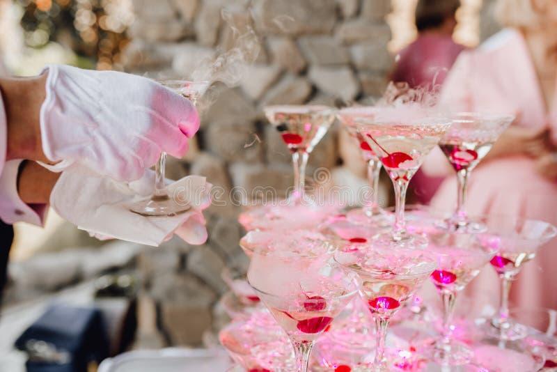 A mão na luva pôs Champagne Glass Pyramid Catering foto de stock