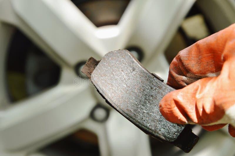 Mão na luva que guarda o forro de freio inválido para mudado no fundo da roda fotos de stock royalty free