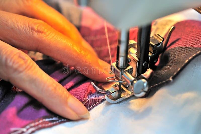 Mão na máquina de costura imagens de stock