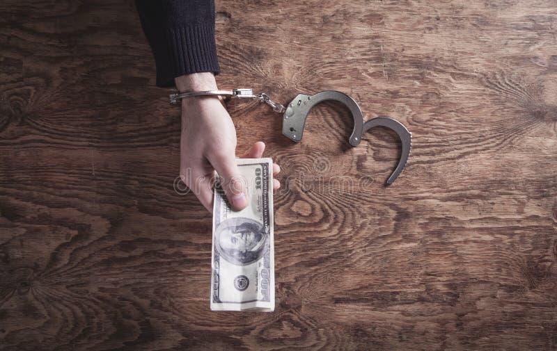 Mão nas algemas que guardam cédulas do dólar corruption imagens de stock royalty free