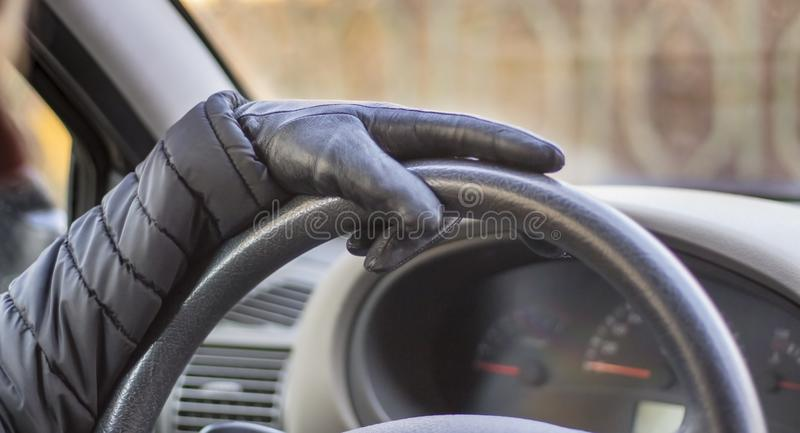 Mão nas luvas pretas que guardam o volante, o conceito da condução imagens de stock