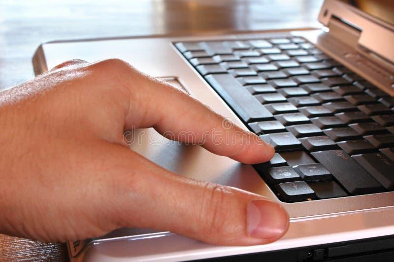 Mão no portátil foto de stock