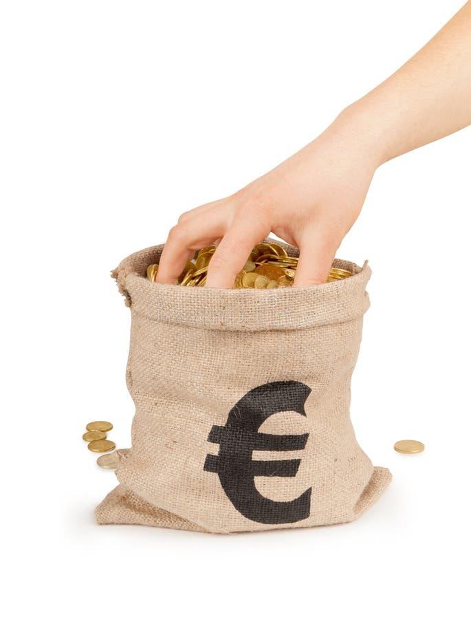 Mão no saco com moedas fotos de stock royalty free