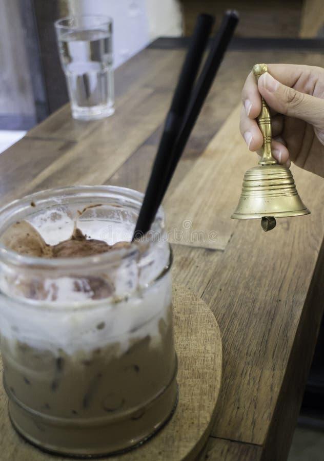 Mão no sino de bronze na cafetaria imagens de stock