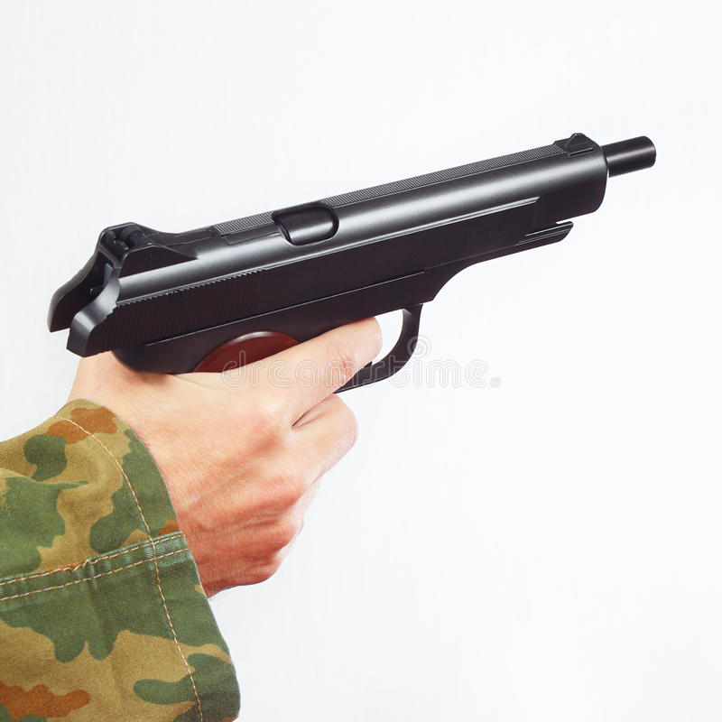 Mão no uniforme da camuflagem com o revólver descarregado no fundo branco imagens de stock royalty free