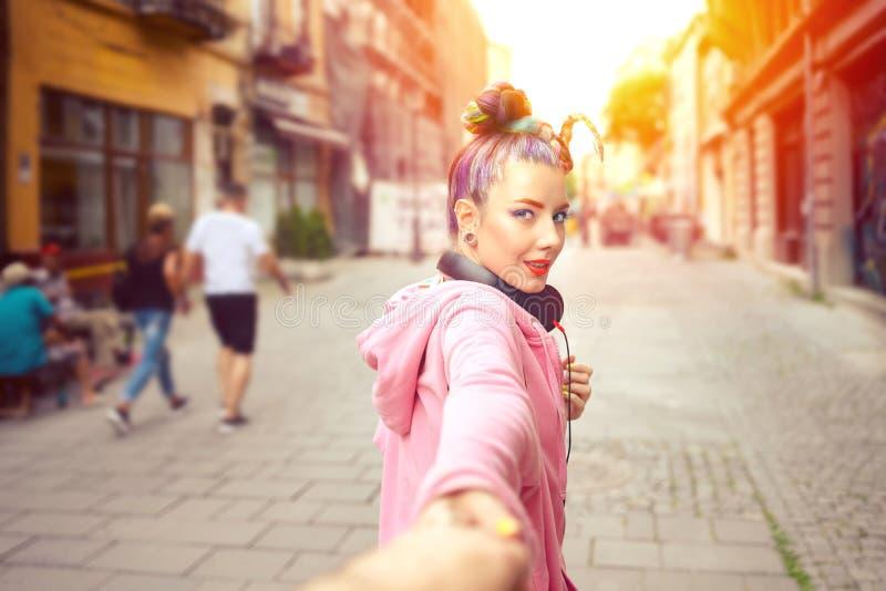 Mão ocasional feliz da terra arrendada da menina do moderno que olha atrás ao andar na rua da cidade fotos de stock royalty free