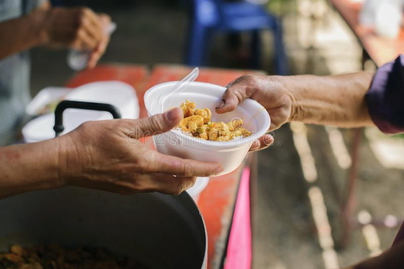 A mão ofereceu doar o alimento de uma parte do homem rico: O conceito da partilha social: Povos pobres que recebem o alimento das imagens de stock