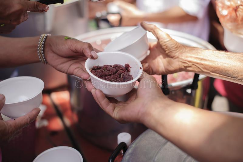 A mão ofereceu doar o alimento de uma parte do homem rico: O conceito da partilha social: Povos pobres que recebem o alimento das fotografia de stock royalty free