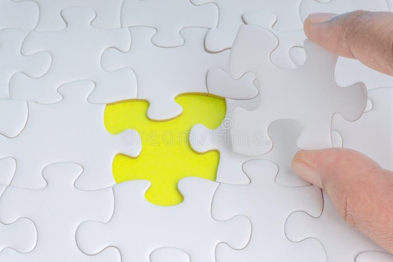 A mão pôs a última parte de close up do enigma de serra de vaivém para terminar a missão imagem de stock