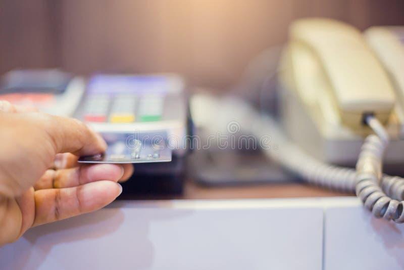 A mão pôs o cartão de crédito no entalhe do leitor e do telefone de cartão do crédito fotografia de stock royalty free